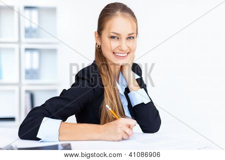 Portrait Of A Beautiful Young Business Woman Doing Some Paperwork In Office