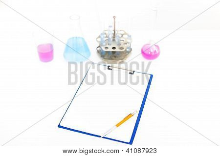 Chemical Flasks With Reagents And Clipboard Isolated Over White Background