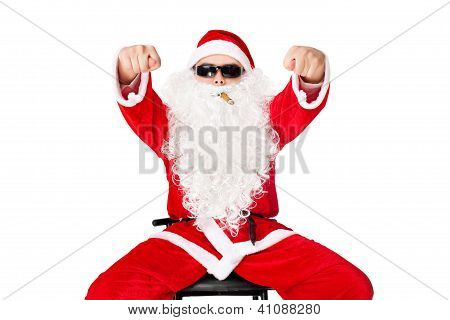 Man In Santa Claus Clothes Sitting In A Chair Wearing Sunglasses With Cigar Shows Fig Isolated On Wh