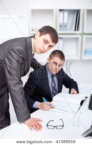 Two Young Businessmen Working Together In Office