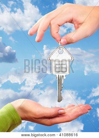 Mano con una llave de la casa. Sobre fondo de cielo azul.