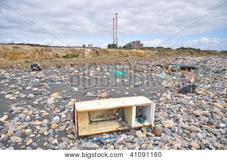 Trashed Fridge On The Seashore Next To A Factory