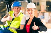 stock photo of forklift driver  - Forklift driver and female super visor with clipboard at warehouse of freight forwarding company  - JPG