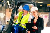 foto of forklift driver  - Forklift driver and female super visor with clipboard at warehouse of freight forwarding company - JPG