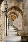 stock photo of beside  - Passage way beside an ancient stone cathedral wall Winchester Hampshire UK - JPG