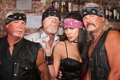 stock photo of gang  - Tough male biker gang members with beautiful woman - JPG