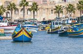 Traditional Luzzu Boat At Marsaxlokk Harbor In Malta.