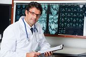 image of radiogram  - Portrait of mixed race male radiologist sitting at desk with clipboard - JPG