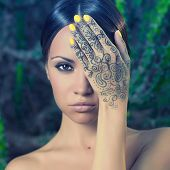 picture of henna tattoo  - Beautiful young lady with painted hands mehendi - JPG