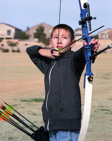foto of fletching  - Young boy archer drawing back a bow and arrow - JPG