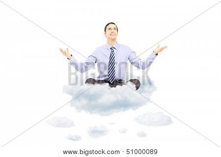Young businessman sitting on a cloud and gesturing with his hands isolated on white background