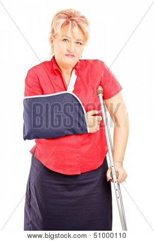 Injured mature woman with broken arm and crutch isolated on white background