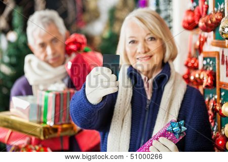 Senior woman holding credit card with man holding presents in background at Christmas store