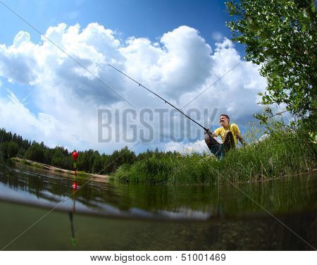 Young man fishing in a pond in a sunny day