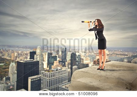career woman looking with binoculars over the city