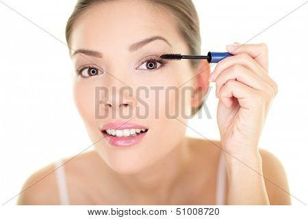 Beauty makeup woman putting mascara eye make up on eyes. Asian fresh face girl looking in the mirror looking at camera isolated on white background. Mixed race ethnic Asian Chinese / Caucasian model.