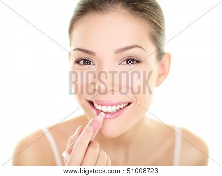 Lipstick makeup woman putting lip balm care. Beauty Asian girl applying color moisturizer on lips getting ready and looking at herself in the mirror smiling happy. Multi-ethnic Asian Caucasian model.