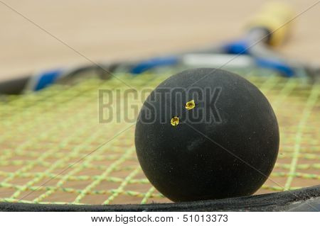 Double Yellow Dot Squash Ball On A Racket