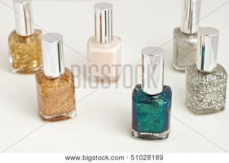 Six different bright nail polish containers against white