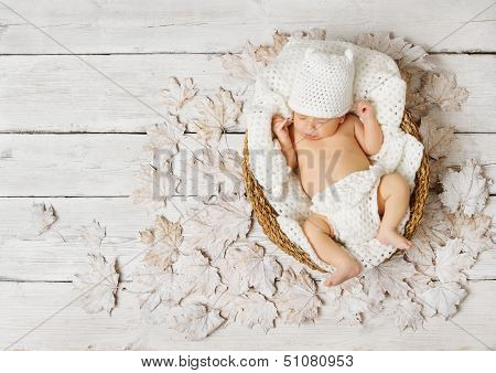 Newborn Baby Sleeping In Basket On Leaves Over White Wooden Background.