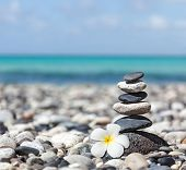Zen meditation spa relaxation background -  balanced stones stack with frangipani plumeria flower cl