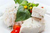 foto of halibut  - Halibut with greens rice and vegetables on white plate - JPG