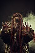 stock photo of maliciousness  - Wicked shaman with bloody hands in smoke - JPG