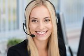 stock photo of hands-free  - Smiling young business woman wearing a headset answering calls at a client service centre or wanting to communicate hands free while continuing to work in her office - JPG