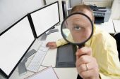 stock photo of crew cut  - The eye of a businessman sitting behind a dual screen computer seen through a magnifying glass illustrating being careful watchful and shrewd in business - JPG