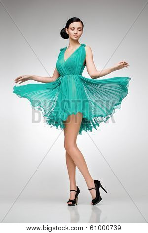 elegant brunette in green dress posing in the studio