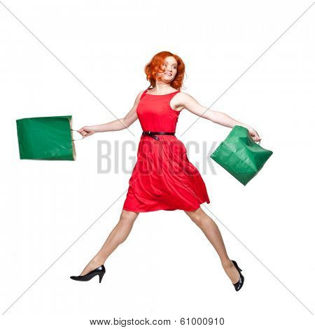 young adult readhead jumping holding green shopping bags in her hands, isolated on white, studio shot