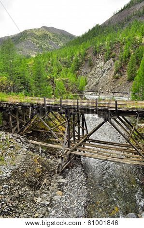 Wooden Bridge In Yakutia Across The Mountain River.