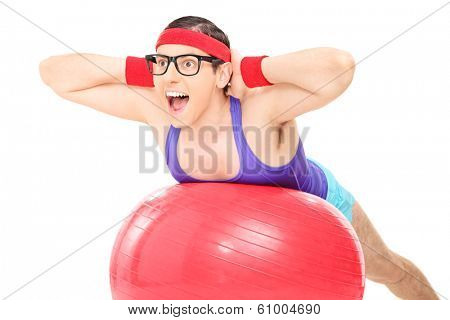 Nerdy guy doing an exercise on a pilates ball isolated on white background