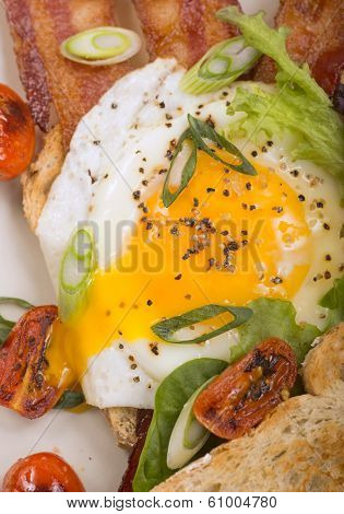 Delicious sunnyside up egg served on toast and bacon with grilled cherry tomatoes