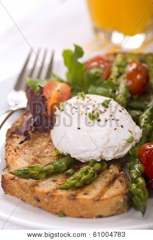Poached egg on toasted bread with asparagus, tomatoes, greens and served with fresh orange juice