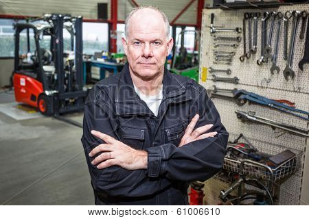 Forklift mechanic stands confident in the garage with a wall of tools and a forklift in the background.