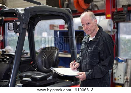 Experienced Mechanic working through a checklist before a brand new forklift is delivered and commissioned in a workshop