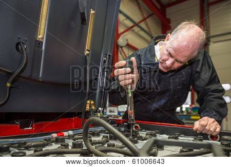 Mechanic measuring the acidity of the batteries in a forklift.