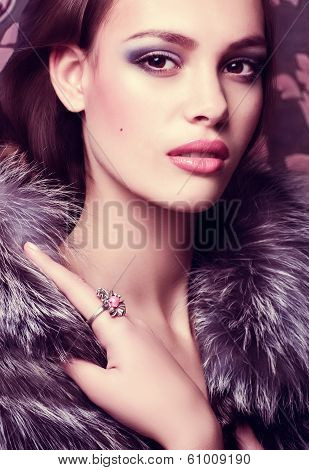 Portrait of beautiful young woman with makeup fur of silver fox