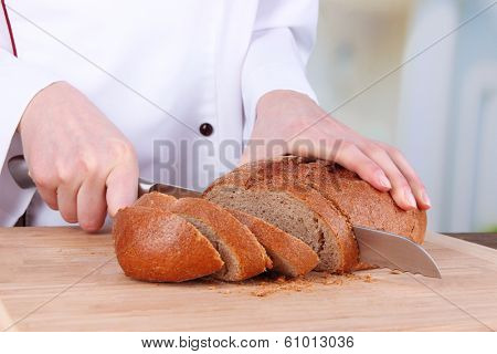 Cutting bread on wooden board on bright background