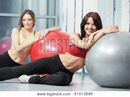 group of young smiling woman with finess ball in gym