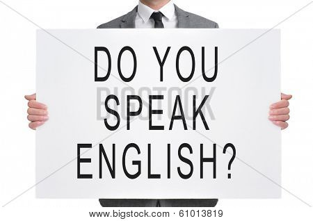 a man wearing a suit holding a signboard with the sentence do you speak english? written in it