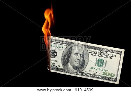 One hundred dollar bill burning on black background