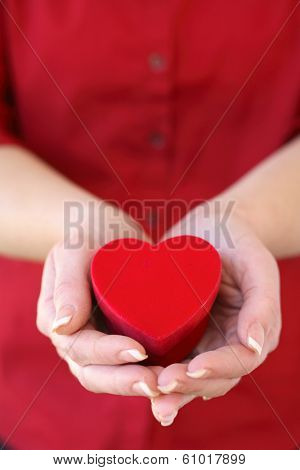Woman holding red heart box in hands in red shirt