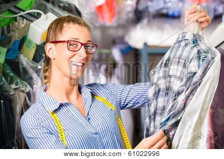 Female cleaner in laundry shop or textile dry-cleaning next to clean clothes in garment bags