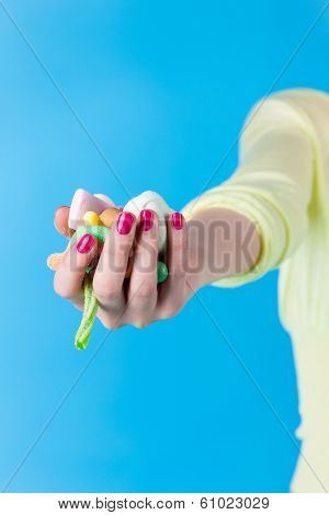 Young woman with many unhealthy sweets or candy in Studio, she have a sweet tooth