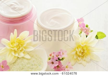 pot of moisturizing face cream and beautiful orchid flowers
