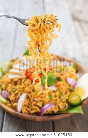 Spicy fried curry instant noodles or Malaysian style maggi goreng mamak.  Ready to serve on wooden dining table setting. Fresh hot with steamed smoke.