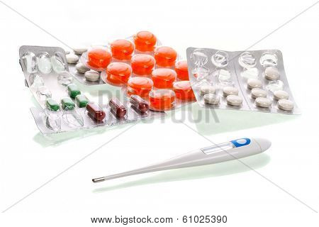 Medical pills and thermometer over white background