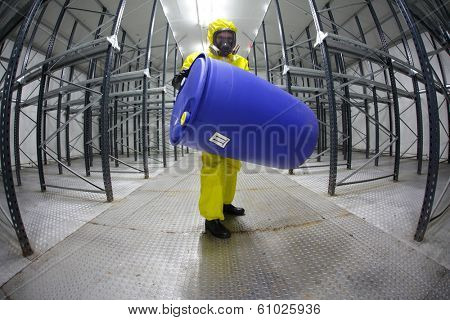 technician protective overalls,mask,gloves and boots lifting barrel of chemicals in empty storehouse - fish eye lens